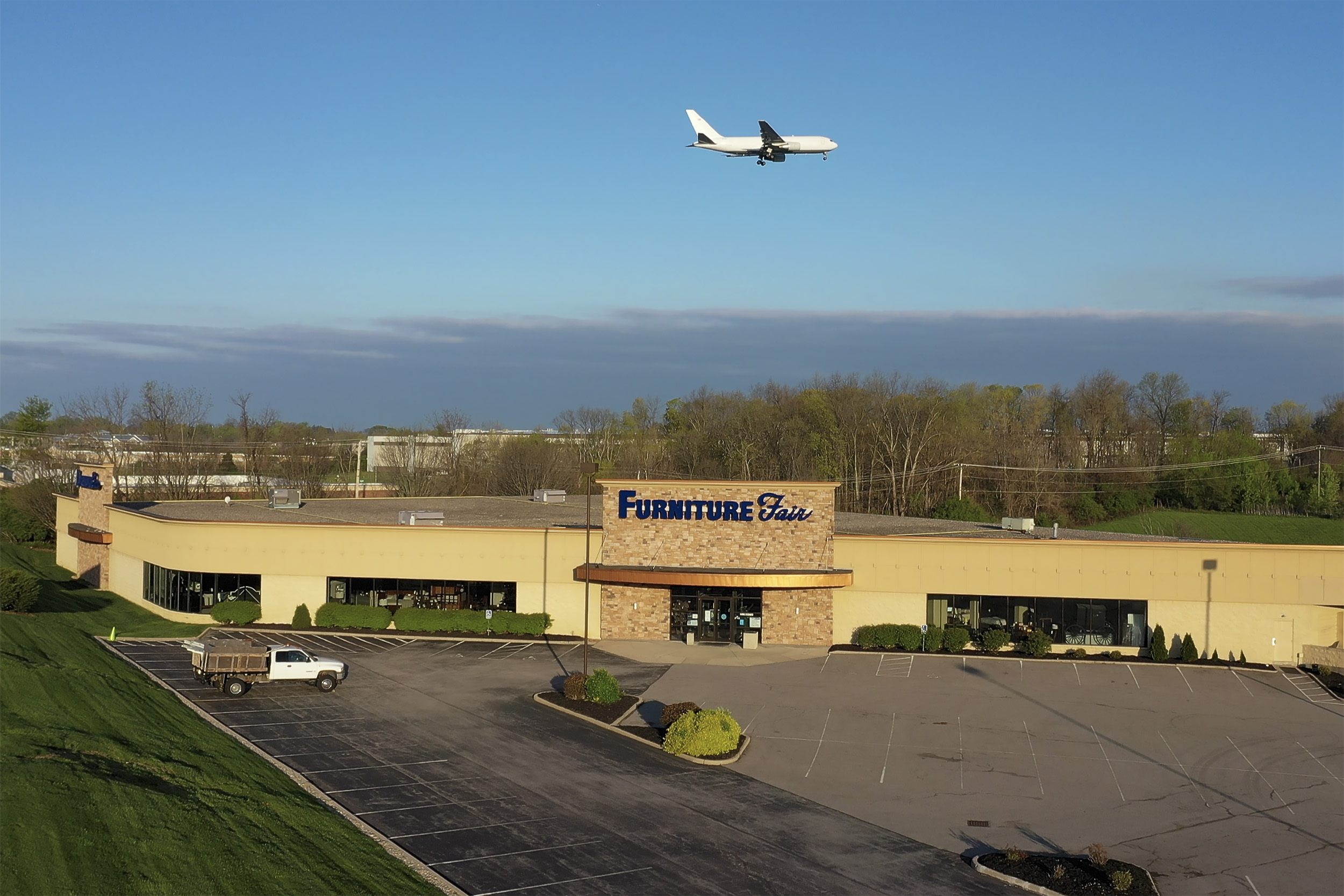 Exterior Drone shot of Furniture Store with airplane flyover